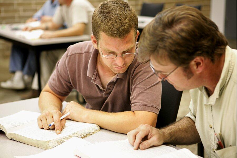 Εκπαιδευτής και μαθητής κατασκευαστής κάθονται σε ένα γραφείο με τον πρώτο να παραδίδει μάθημα θεωρητικής εκπαίδευσης βάσει του προγράμματος Τεχνικής Κατάρτισης