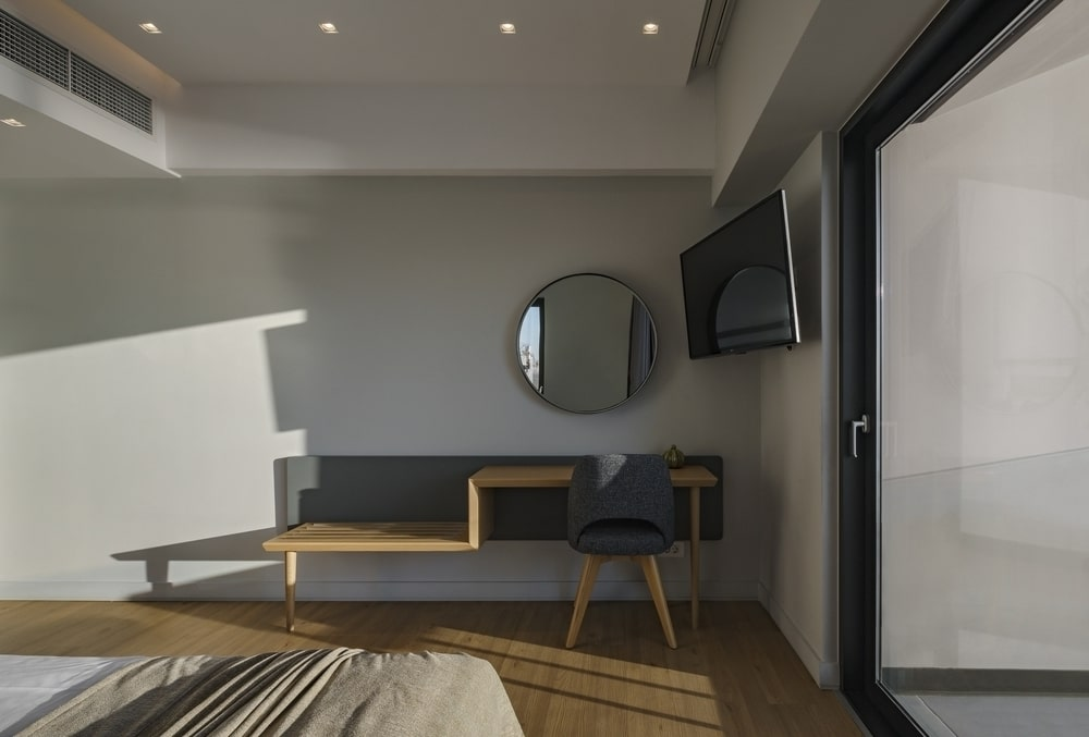 Desk with chair and mirror, large TV hanging on the wall