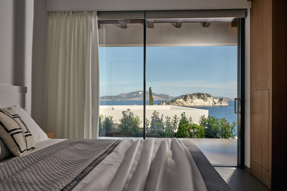 Bed with view to the sea through the aluminum window