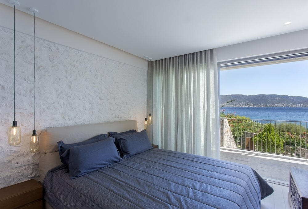 Master bedroom with open curtains and sea view
