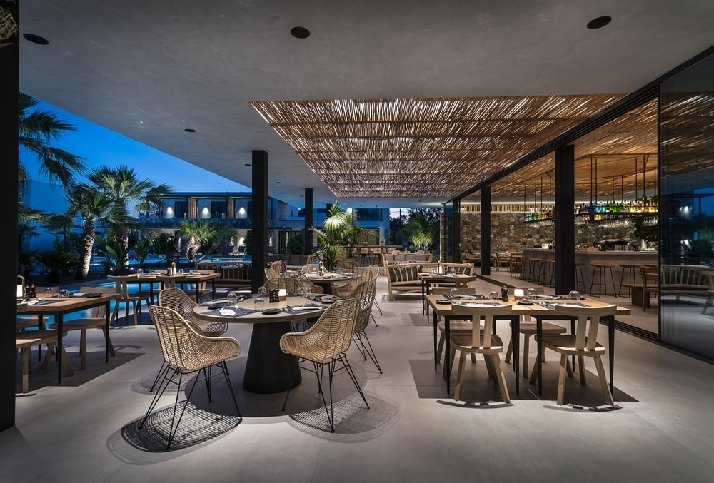 Outdoor area with tables and chairs by night