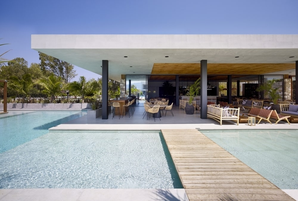 A path on top of the pool, leading to the outdoor area with chairs and sofas