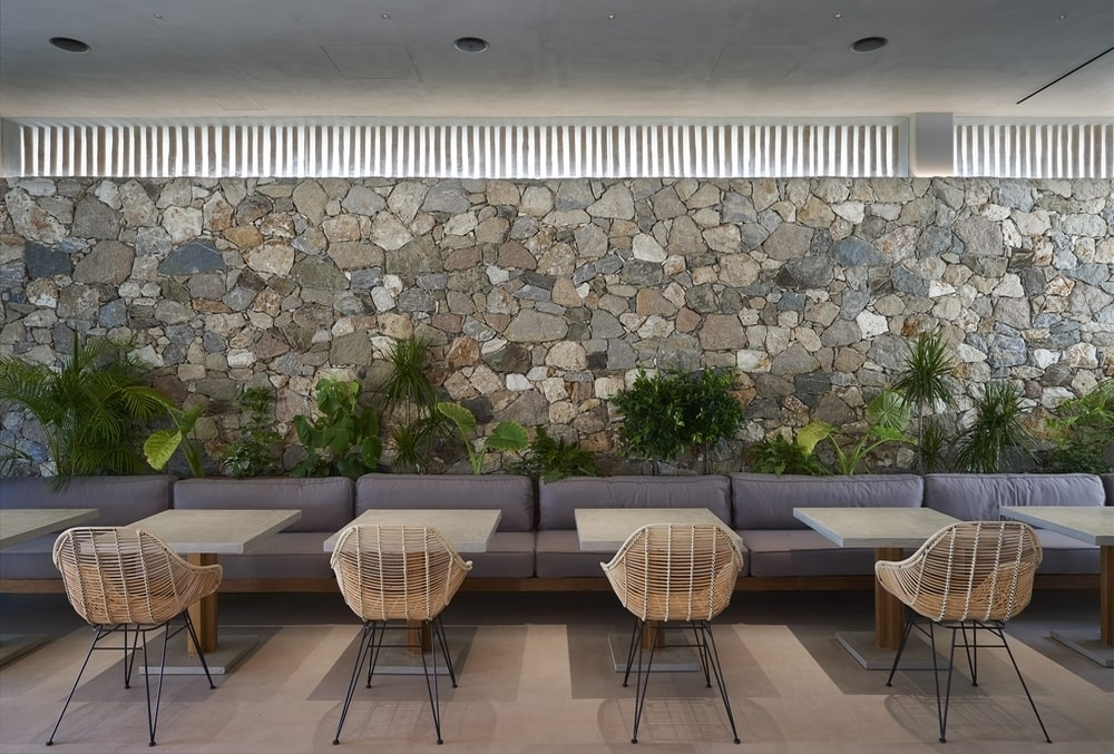 Large sofa, chairs and tables in front of a large rock wall