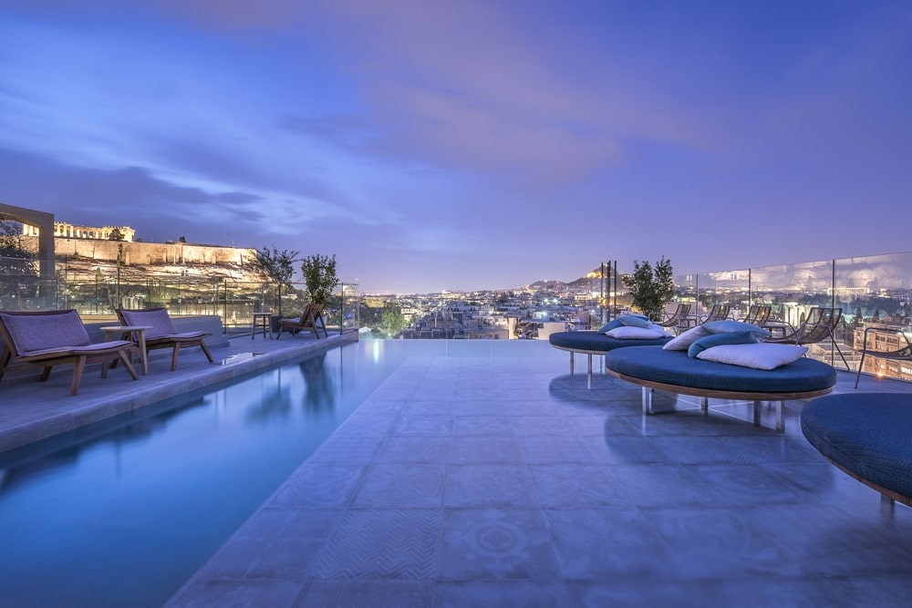 Pool with round sunbeds with view to the city and the Acropolis at night