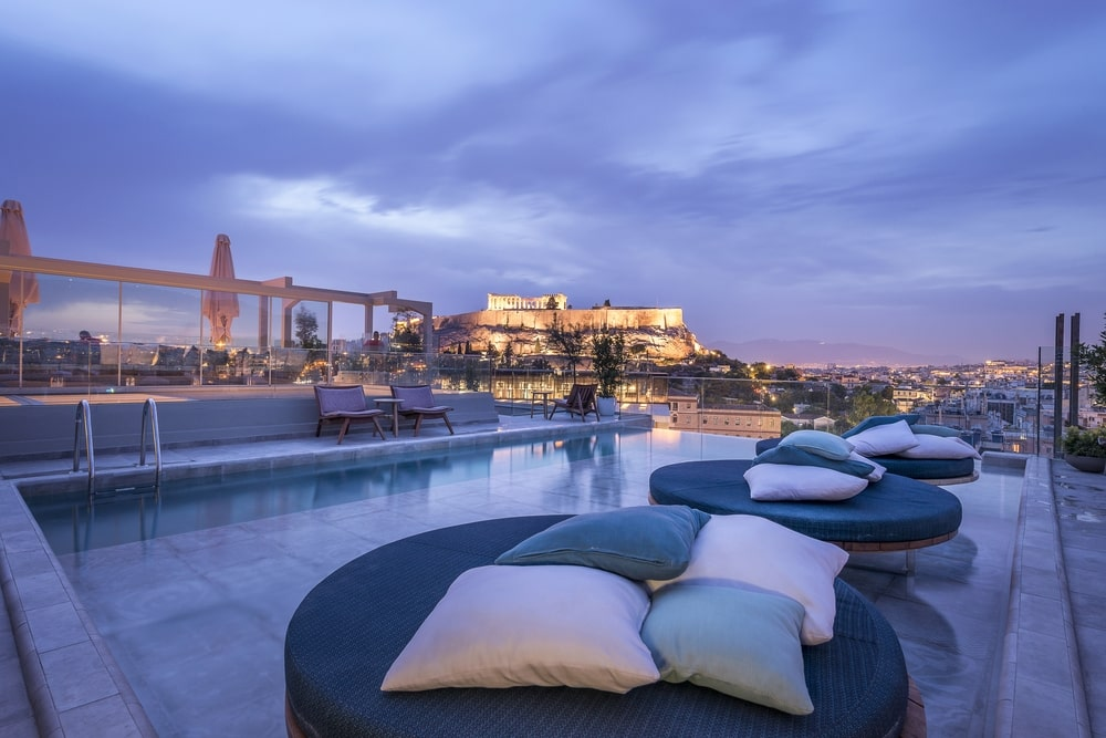 Pool with round sunbeds with cushions and view to the Acropolis at night