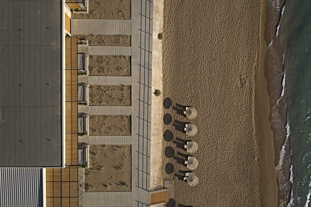 Beach with sunbeds and hotel courtyard from above