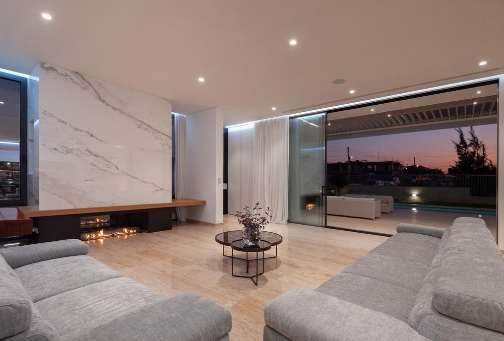Living room with large sofas and fireplace, open aluminum windows with view to the terrace
