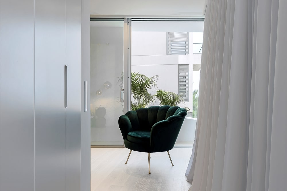 Stylish chair in white room with window and curtain