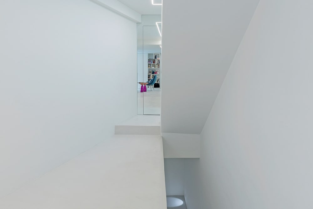 White corridor with colorful sitting room in the back