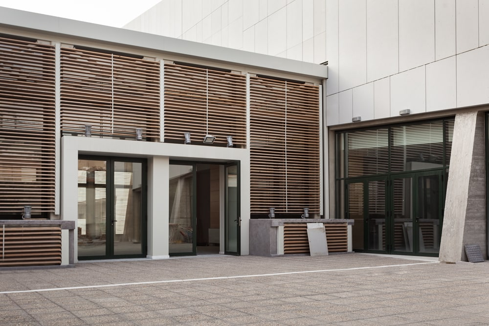 The building entrance has wooden shading around the two doors