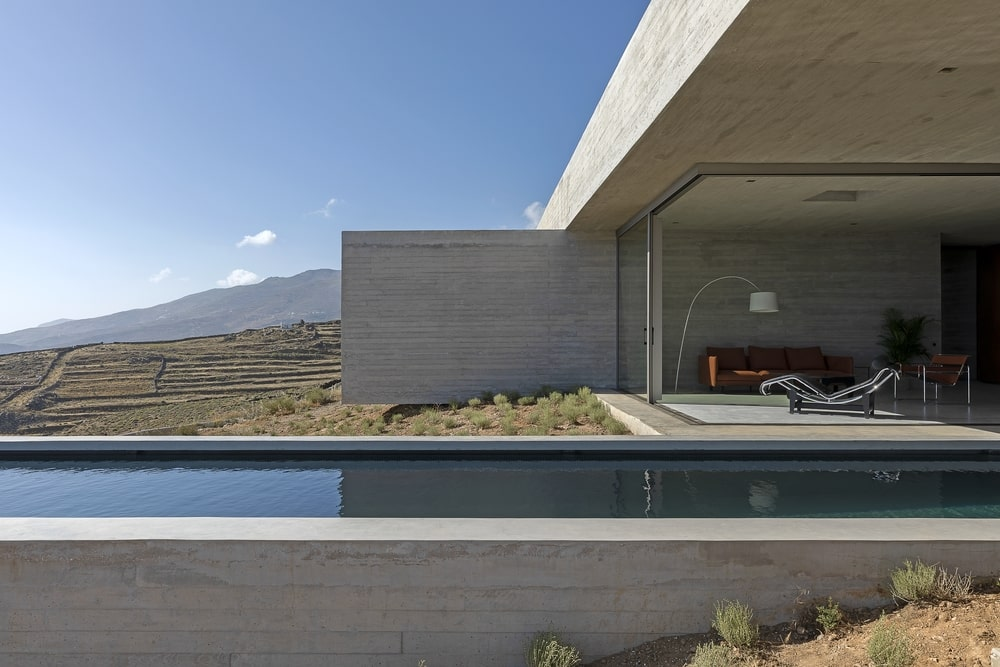 Pool with living room and concrete wall in the back