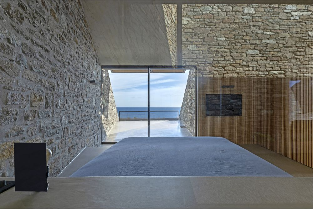 The bedroom has stone walls and a window with sea view