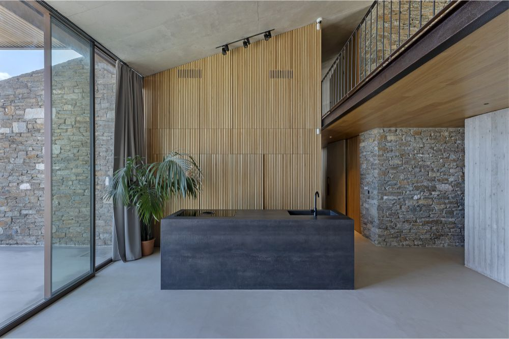 The kitchen counter is a concrete block in front of a wooden wall and a large window