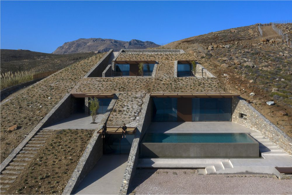 The house is built in the ground, three storeys with windows and a pool appear