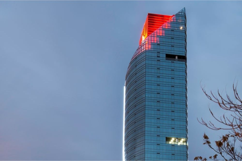 the glass tower has a red section coming through the angled top