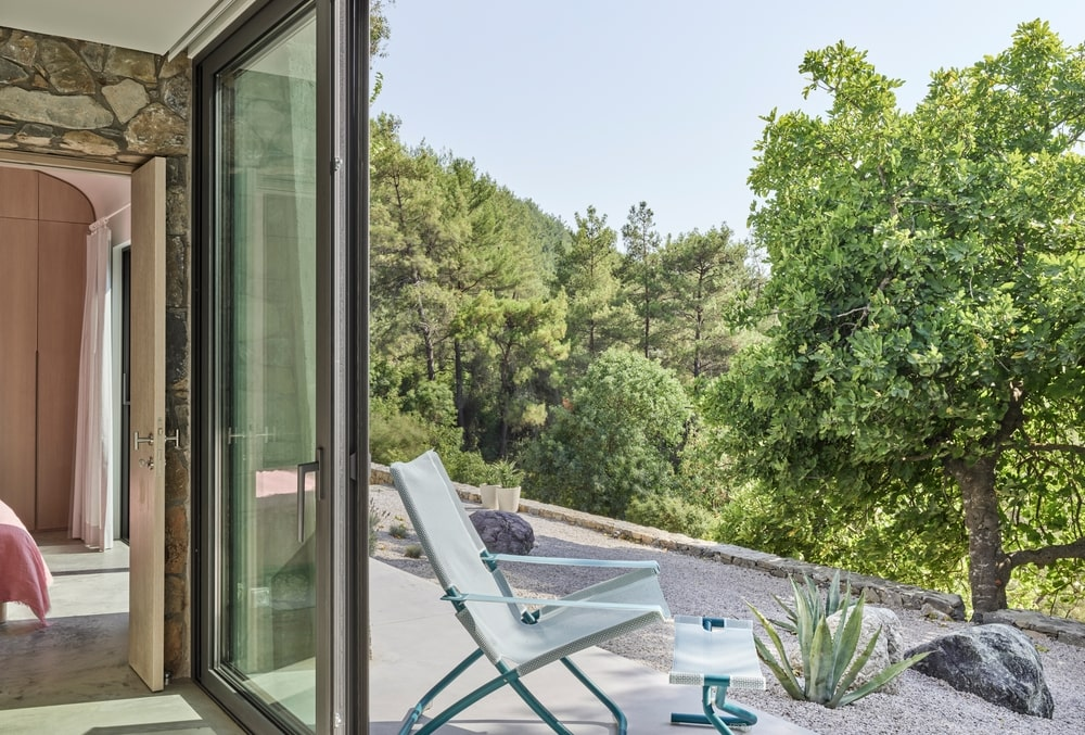 Open aluminum window with terrace and forest view