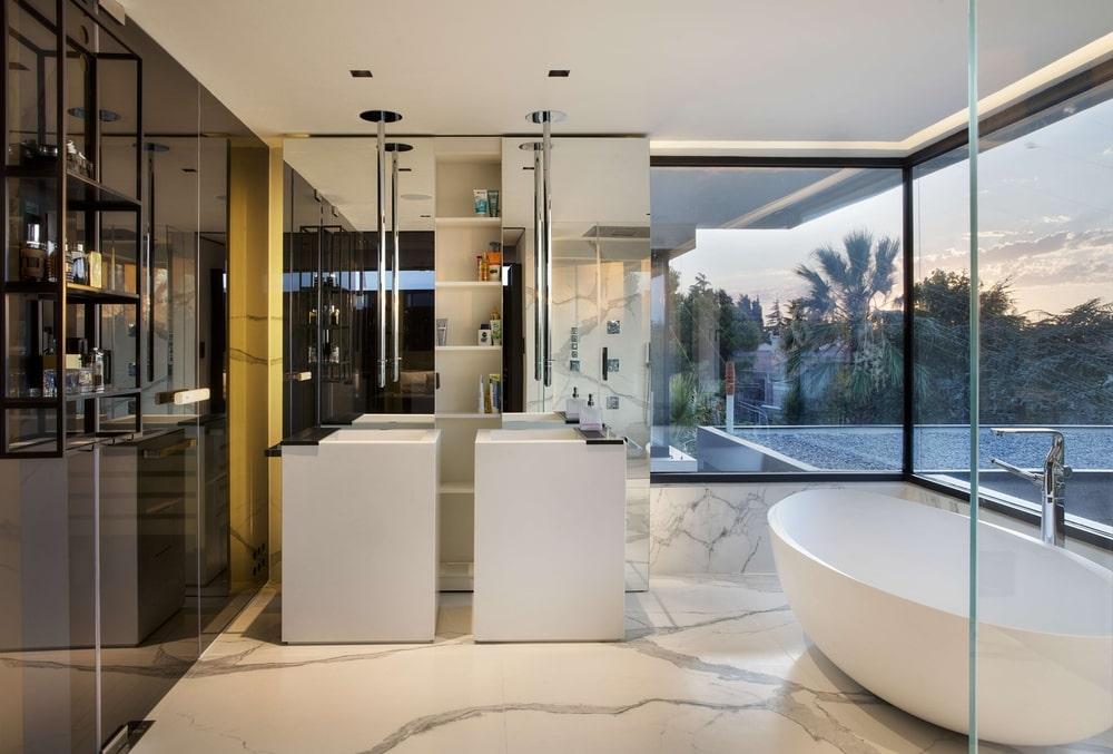 Bathroom with two sinks and bathtub next to window
